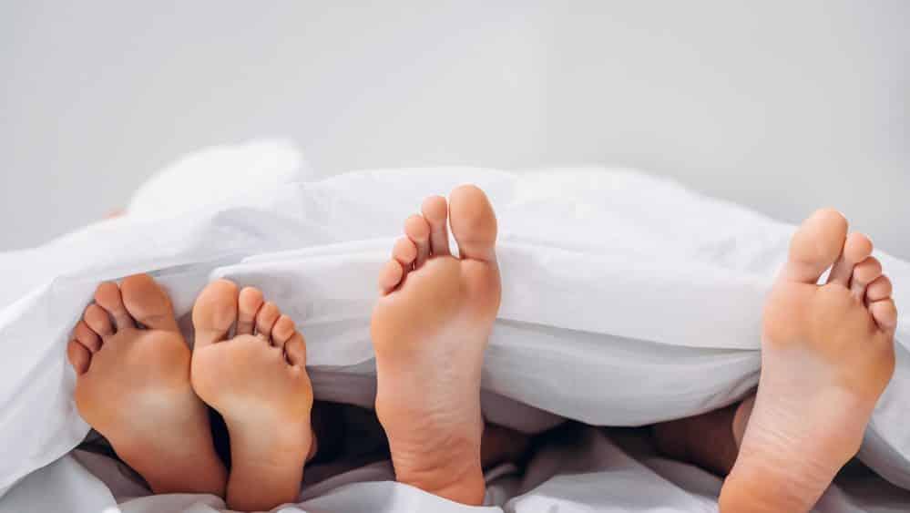 pés de homem e mulher deitados na cama e cobertos com lençol