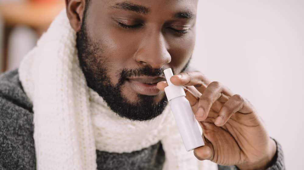 homem aplicando descongestionante nasal