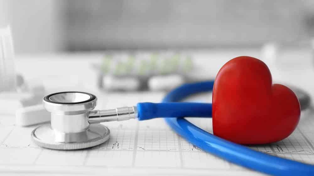 Estetoscópio, pílulas e coração vermelho com um eletrocardiograma