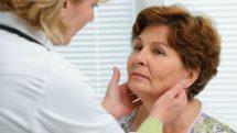 médica examinando pescoço de paciente mulher