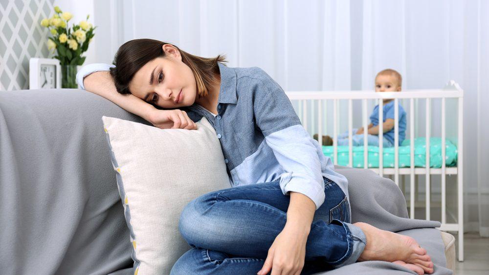 mãe com depressão pós-parto encostada no sofá com bebê ao fundo