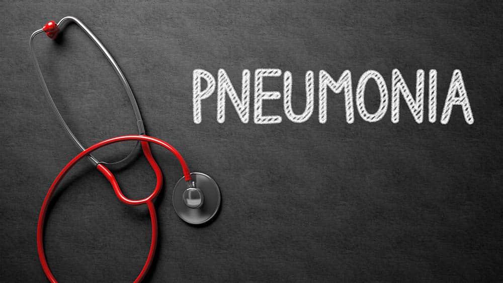 Pneumonia escrito em uma lousa e estetoscópio ao lado.