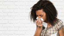 menina enxuga nariz com lenço ao espirrar. Gripes e resfriados não são sinônimos