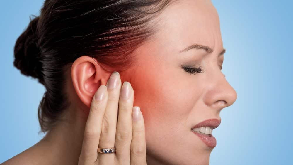 mulher com mão no lado da face, em sinal de dor. neuralgia do trigêmeo atinge um dos lados da face