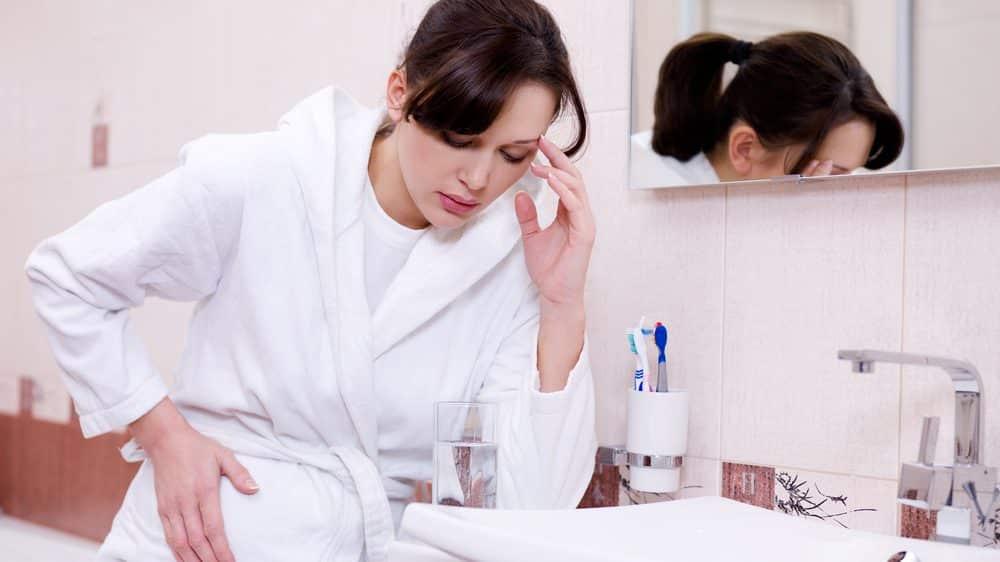 mulher no banheiro, com enjoo. náuseas na gravidez são comuns
