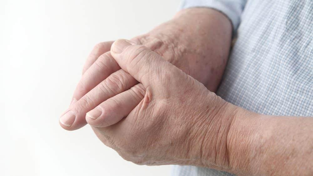 close em mão de idoso com dor nas articulações devido à artrite