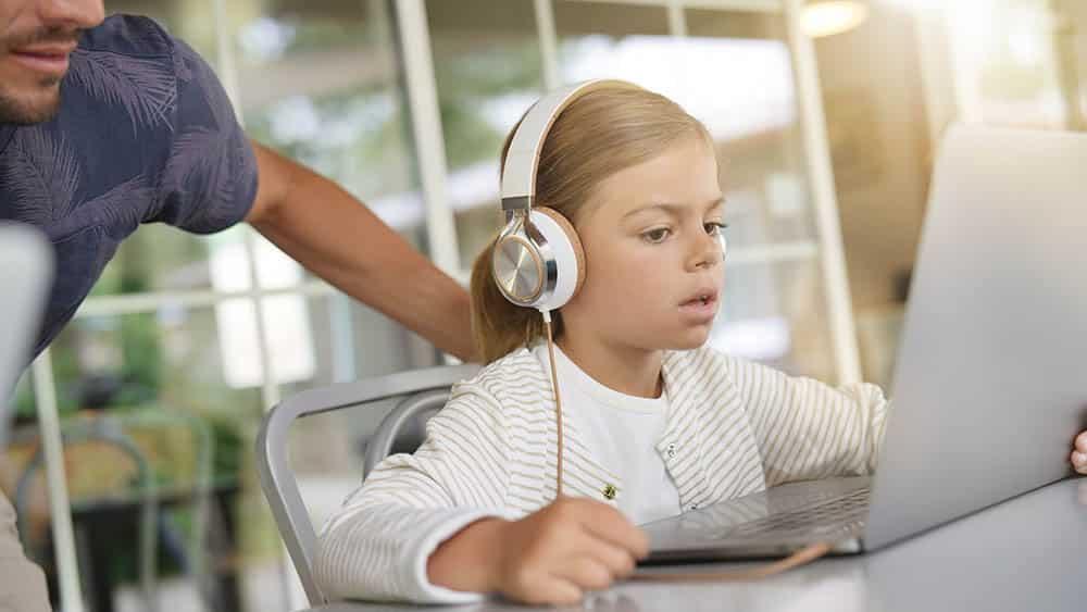 Menina usando notebook com pai ao lado.
