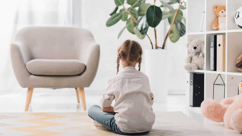 Menina sozinha de costas sentada no chão.