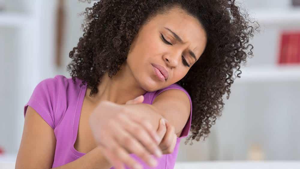 Mulher com a mão da região do cotovelo e expressão de dor.