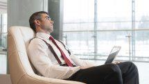 Homem sentado olhando pela janela com expressão de tédio.