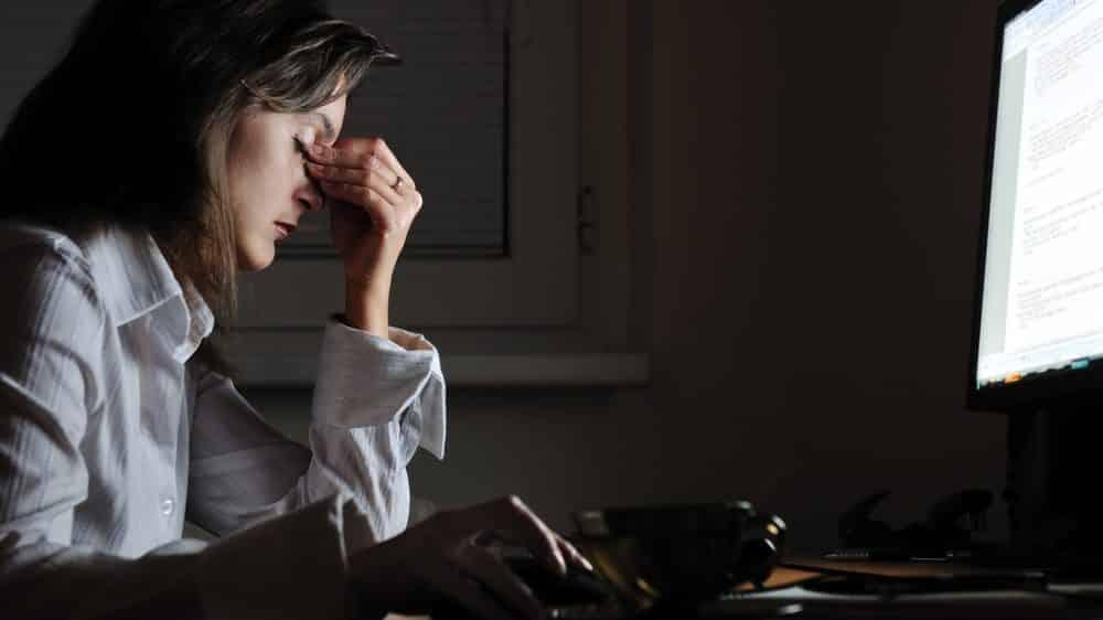 mulher trabalhando diante do computador à noite, com a mão no rosto em sinal de estresse