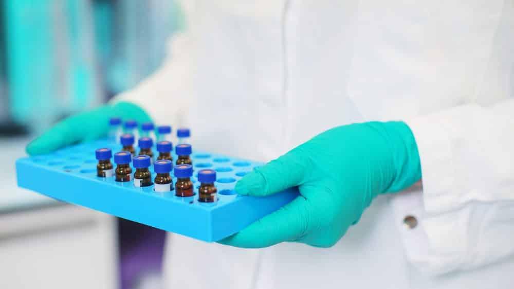 técnica de laboratório segura bandeja com frascos, em local de produção de vacinas