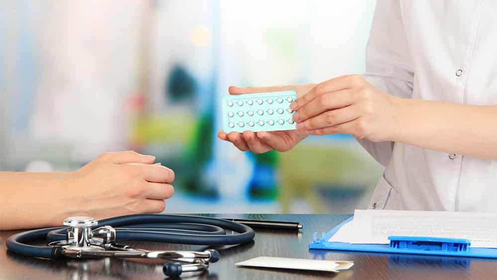 Ginecologista entregando cartela de anticoncepcionais para paciente,