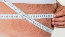Homem obeso se medindo com fita métrica.