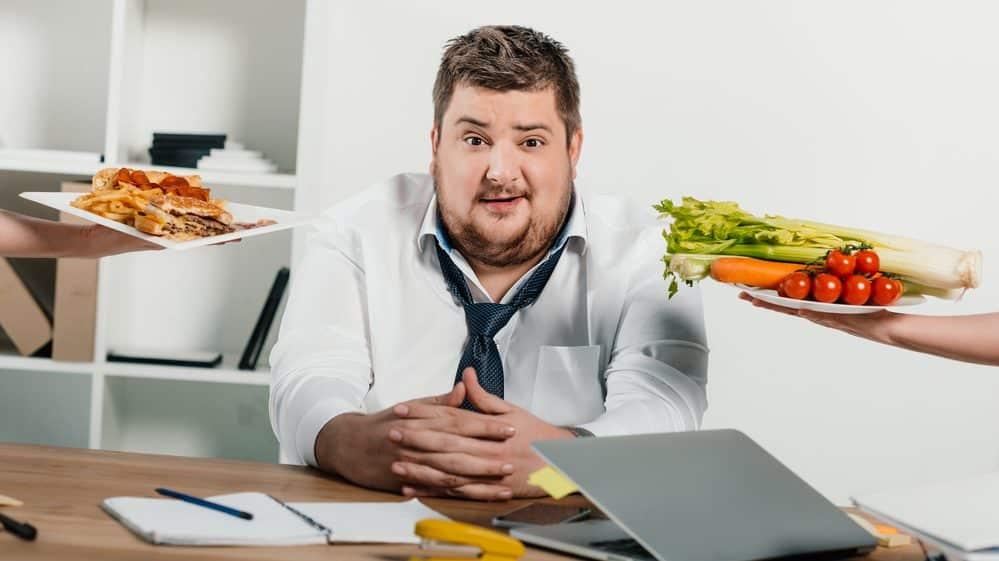 homem gordo sentado enquanto lhe oferecem salada e sanduíche. Dietas para emagrecer não devem ser muito restritivas.