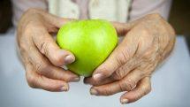 Close em mãos de mulher mais velha com deformidades de artrite segurando uma maçã verde.