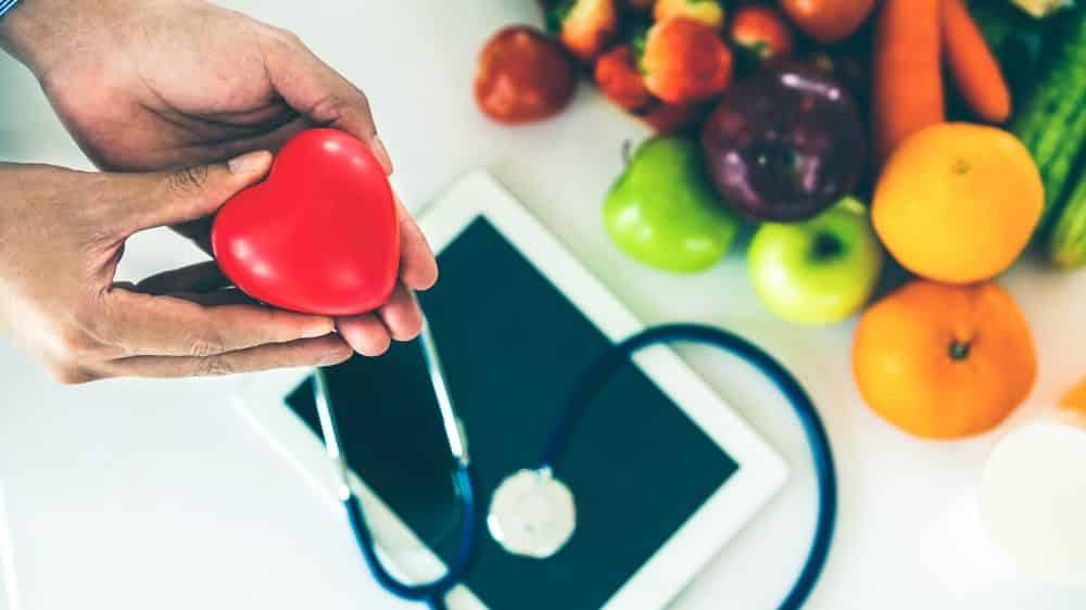 homem segura modelo de coração com frutas, esteto e ipad ao fundo. Há controvérsias sobre o colesterol entre médicos