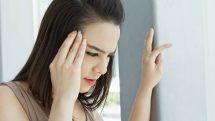 Mulher com uma mão na cabeça e outra apoiada na parede, indicando sinais de tontura, sintoma clássico de pressão baixa.