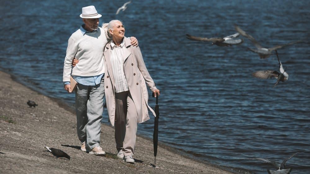casal de idosos caminha na beira do mar. longevidade e amadurecimento sexual têm ligação