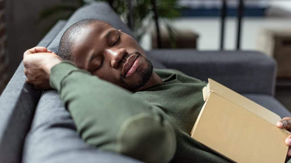 homem dorme no sofá com livro aberto sobre o peito. estudo mostra relação entre falta de sono e diabetes