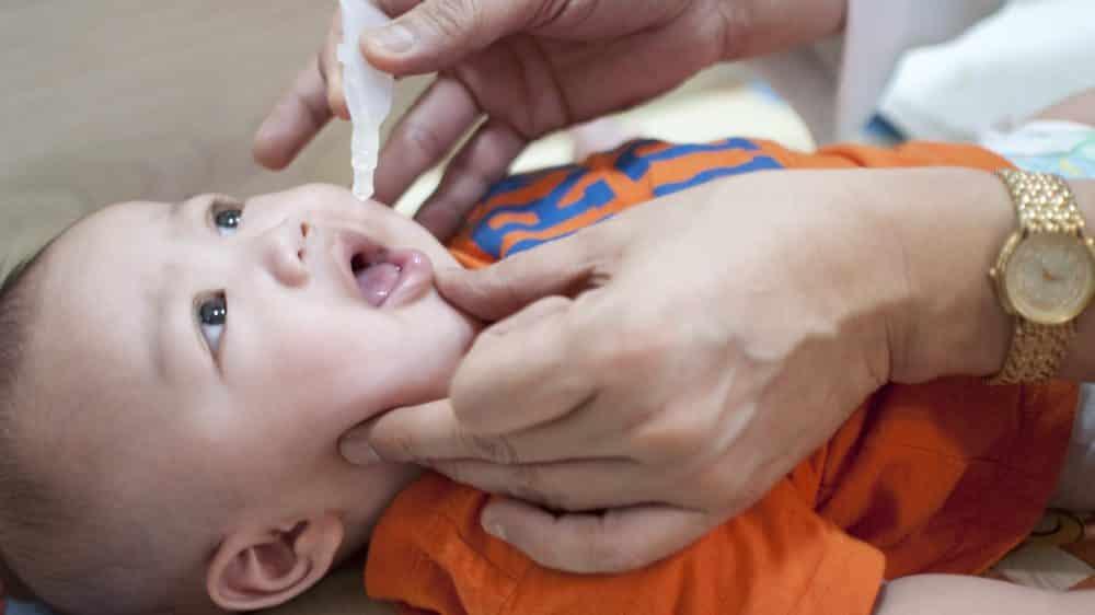 bebê toma vacina de gotinha. vacina permitiu o fim da poliomielite em vários países