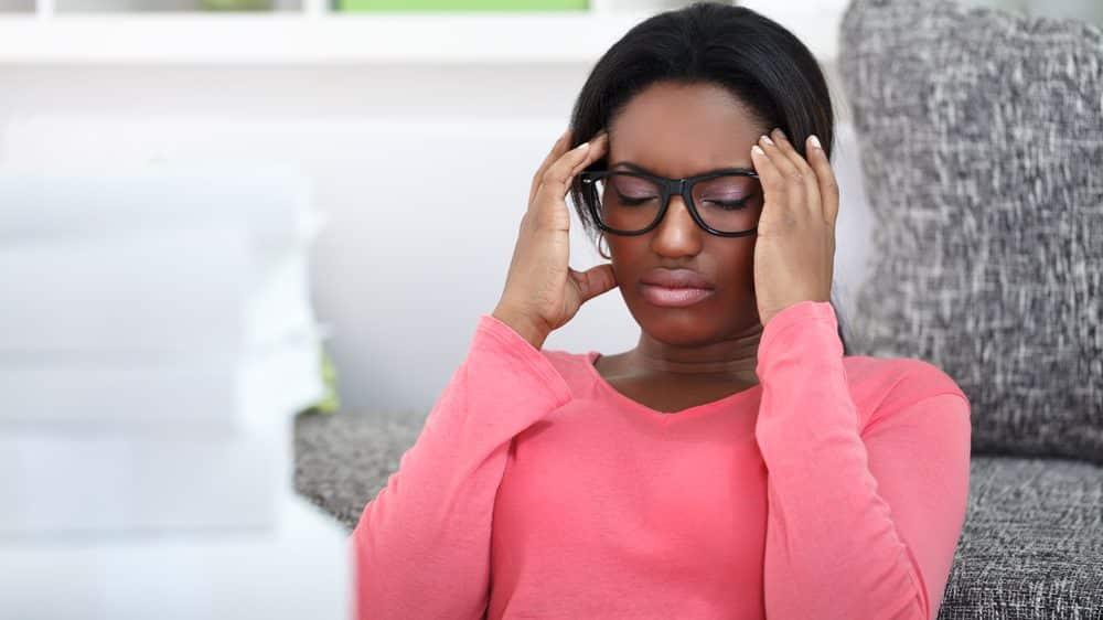 mulher com mãos na cabeça em sinal de dor