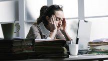 Executiva em frente a um notebook com as mãos nas laterais da cabeça e olhos fechados indicando dor.