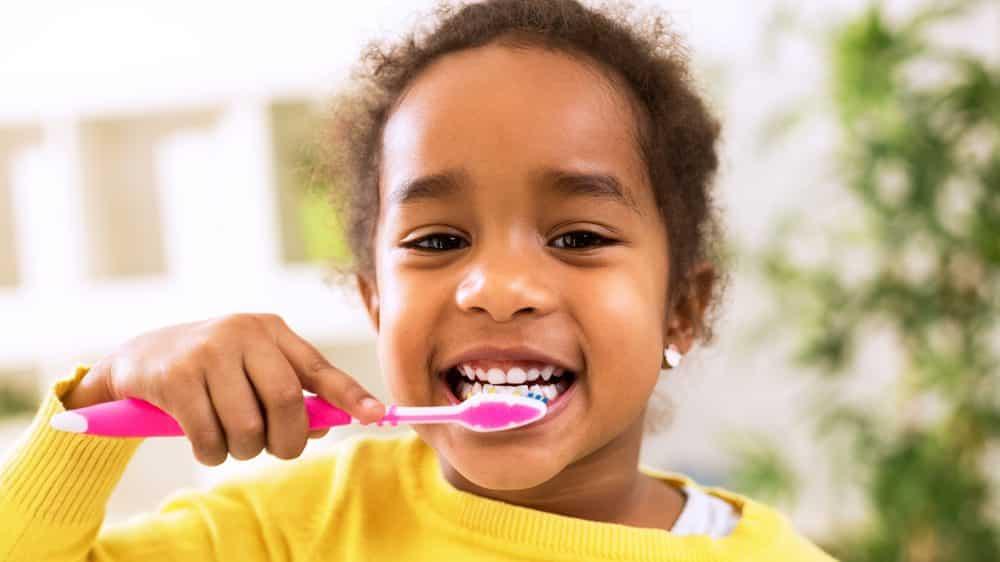 menina pequena escova os dentes. evolução dos dentes foi enorme nos últimos séculos