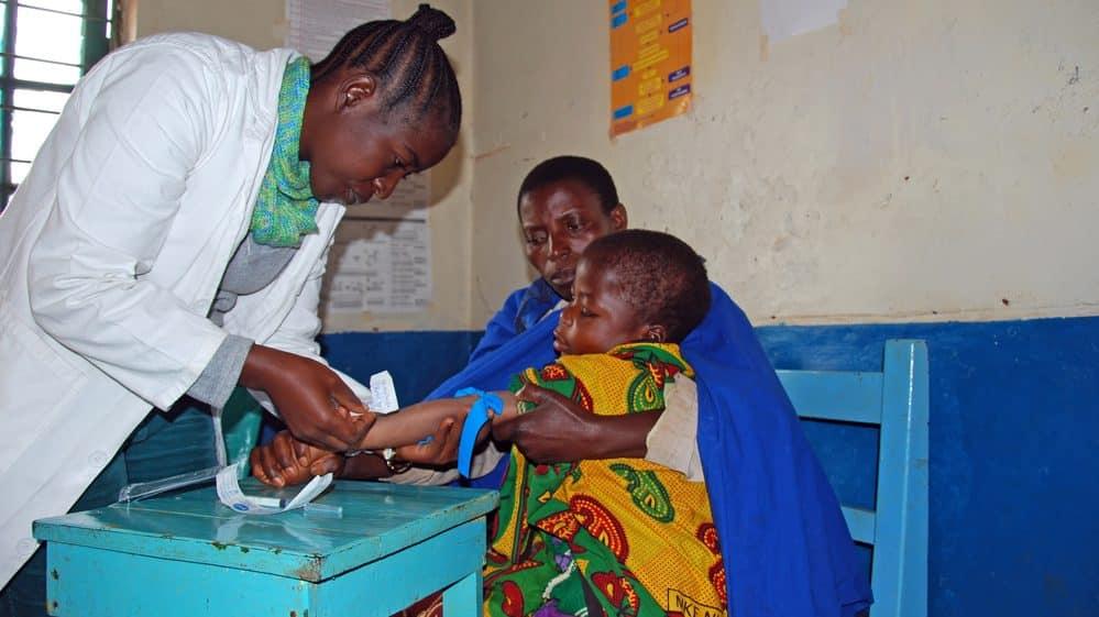 médica de médicos sem fronteiras faz teste de aids em criança sentada no colo do pai na Tanzânia