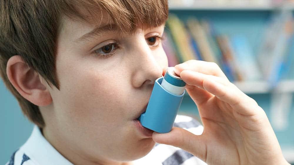 Menino usando bombinha usada para tratar asma.