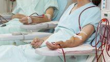 Mulher sentada fazendo diálise com outro paciente desfocado ao fundo.