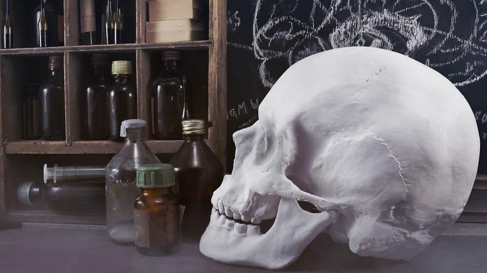 crânio e vidros de remédios antigos sobre balcão, simbolizando duzentos anos de medicina