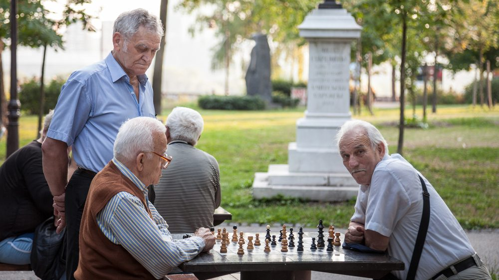 idosos jogam xadrez em praça pública. melancolia lusitana aparece na vida de portugueses
