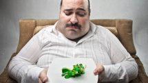 homem obeso diante de prato de salada. Dieta restritiva é comum em spa