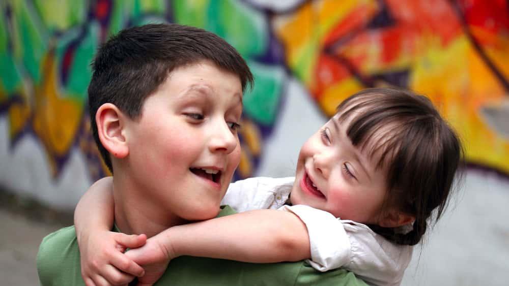 Menina com síndrome de Down sorrindo é carregada por menino