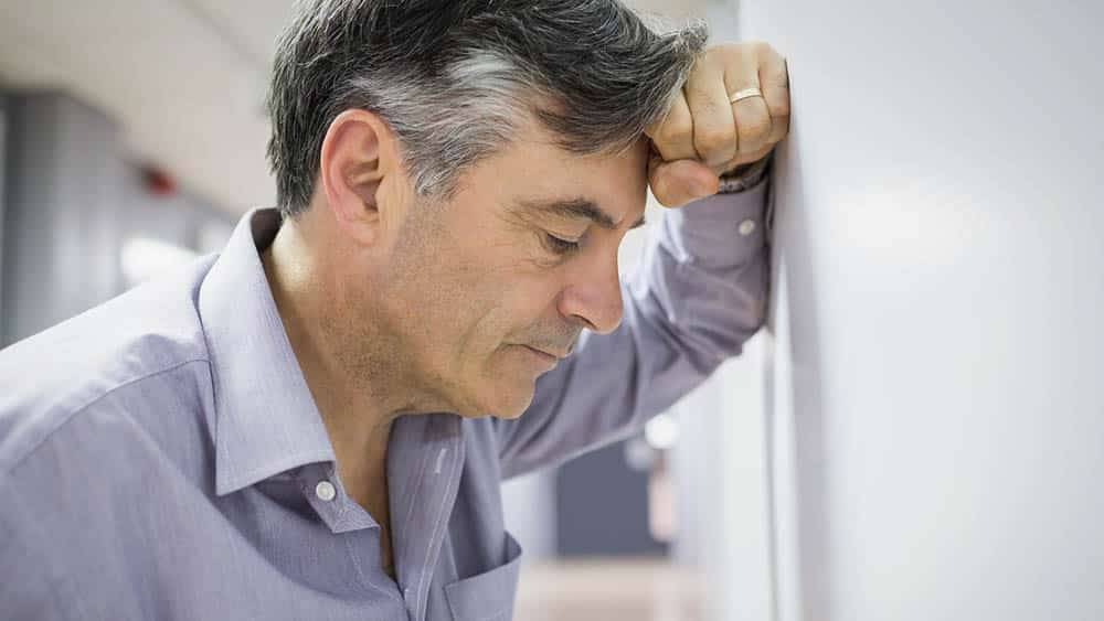 Homem com mão apoiada na parede e cabeça sobre a mão, indicando estresse e cansaço.