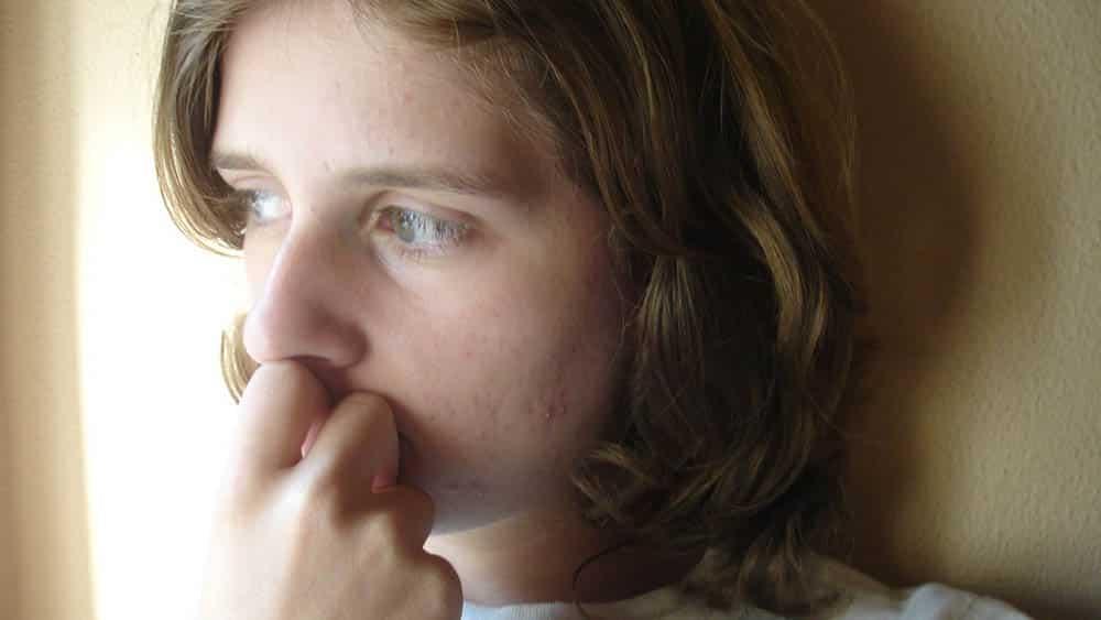 Close em rosto de mulher jovem com olhar distante.