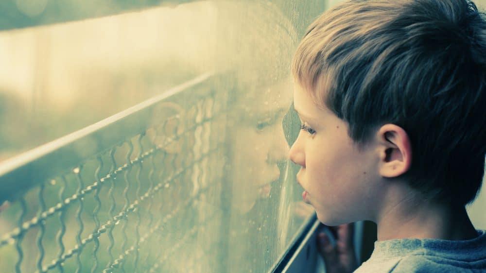 Menino pequeno olhando pela janela. Diagnóstico de transtorno do espectro autista no Brasil nem sempre é feito corretamente.