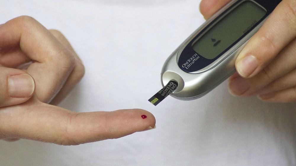 Teste de diabetes realizado a partir de uma picada no dedo indicador.