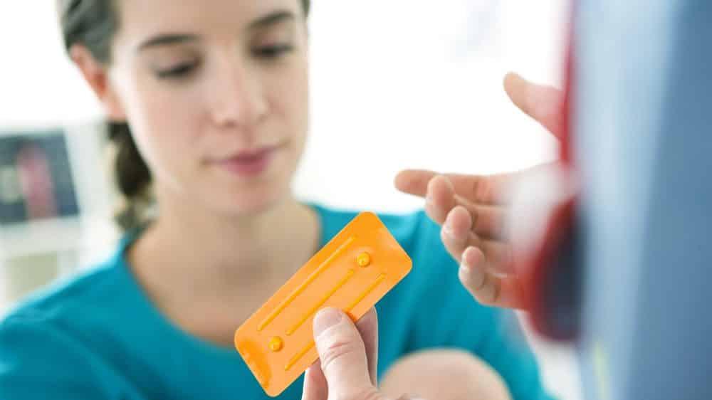 médico mostra cartela de pílula do dia seguinte para paciente