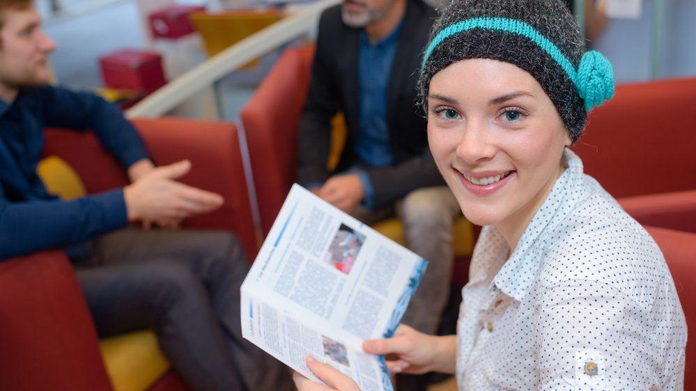 mulher com gorro lê livro. Pacientes com câncer sofrem mais no inverno