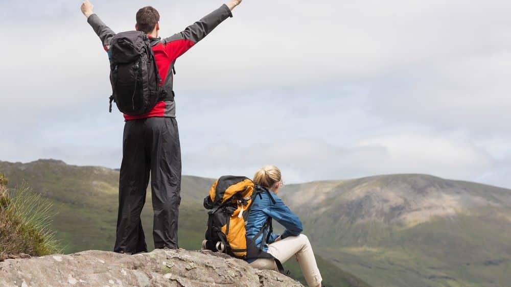 casal de costas no alto da montanha. Alpinistas têm risco de sofrer mal da montanha.