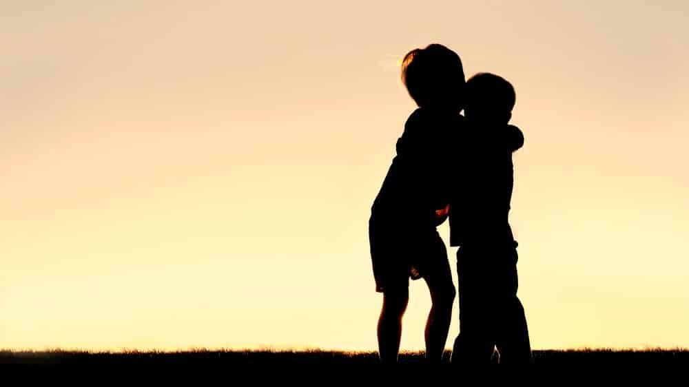silhueta de dois meninos abraçados. paixão arrebatadora destruiu amizade antiga