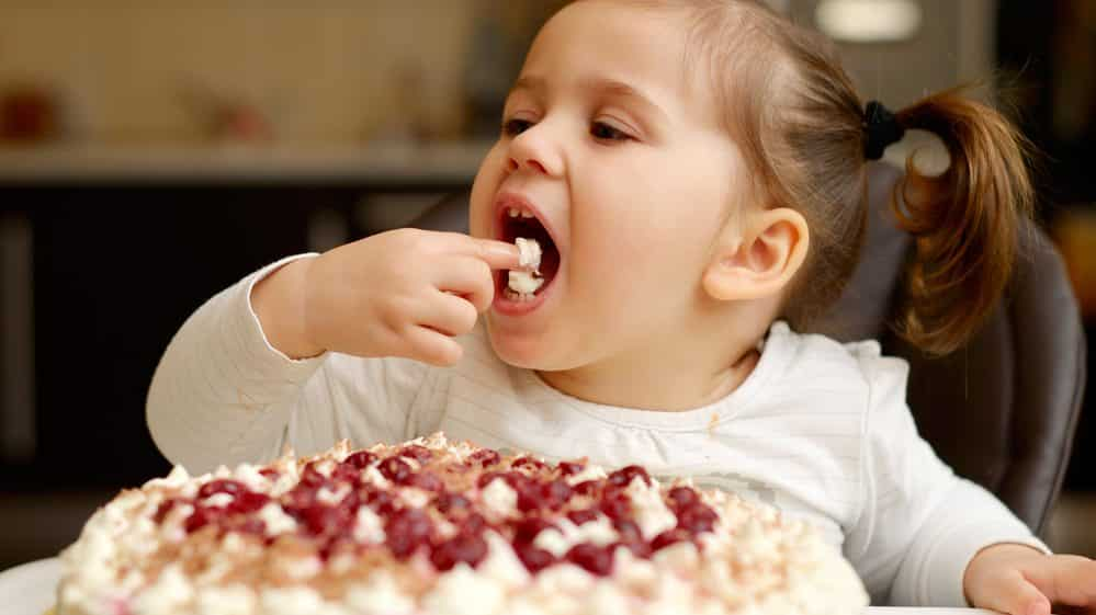 menina comendo bolo. mecanismos envolvidos no comer compulsivo são semelhantes aos do vício
