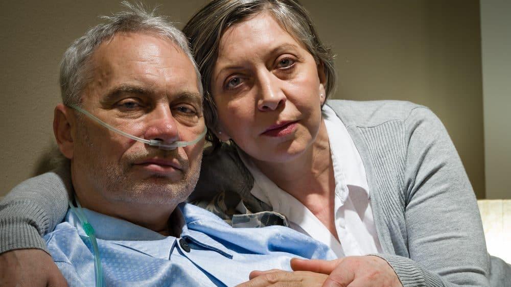 homem faz uso de oxigênio ao lado da esposa. Oxigenoterapia é indicada para casos de obstrução pulmonar crônica