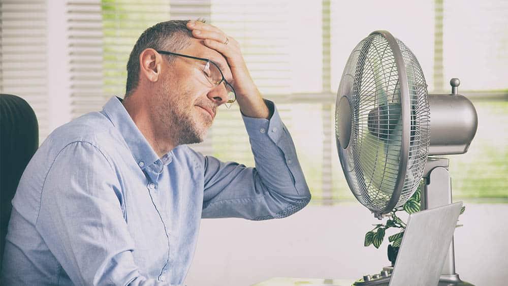 Homem em escritório com mão na testa em frente a ventilador.