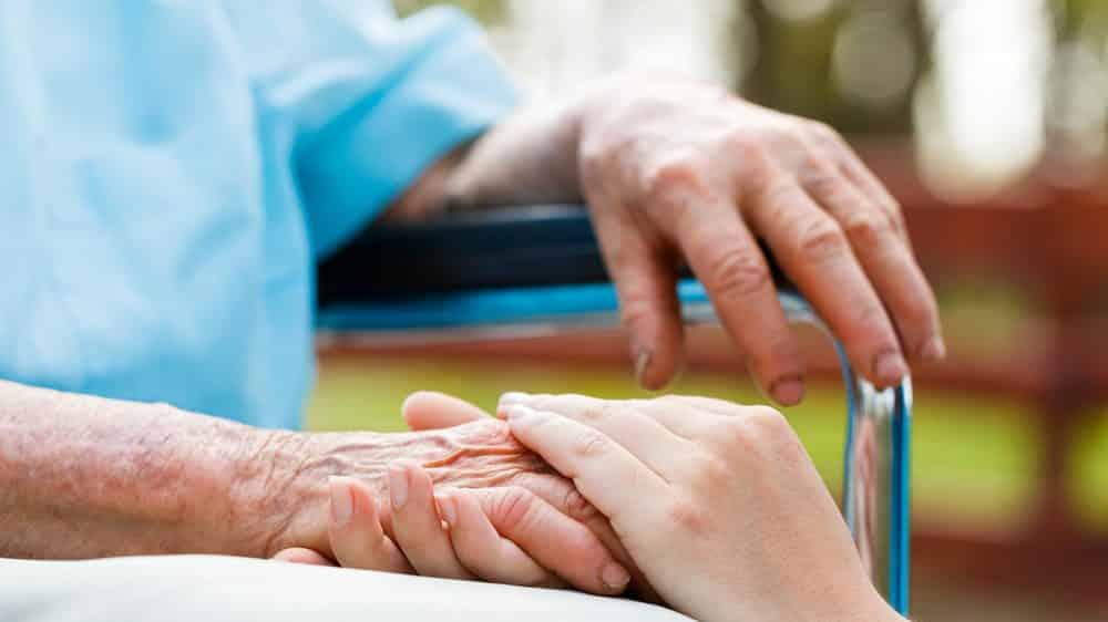 mãos de idoso segurando a mão de mulher jovem. solidariedade feminina é sempre maior