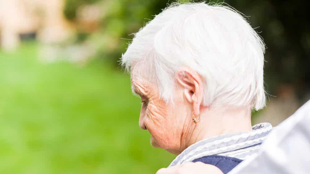 mulher idosa de costas, sentada. incidência de demência vem diminuindo