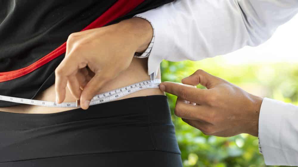 médico mede circunferência abdominal de mulher