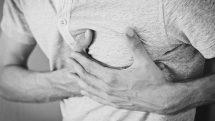 Homem com as mãos no peito, demonstrando sentir dor.